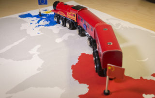 Toy train on map of China and Europe.